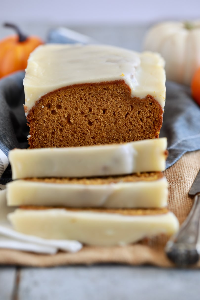 Sliced pumpkin bread with a glaze on top.