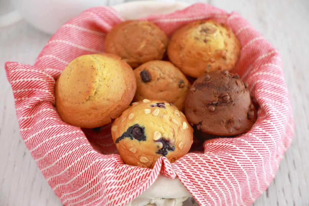 Basket with blueberry and oat muffin, double chocolate muffin, apple cinnamon muffin, carrot cake muffin, lemon and poppy seed muffin, banana nut muffins, all made from one recipe.