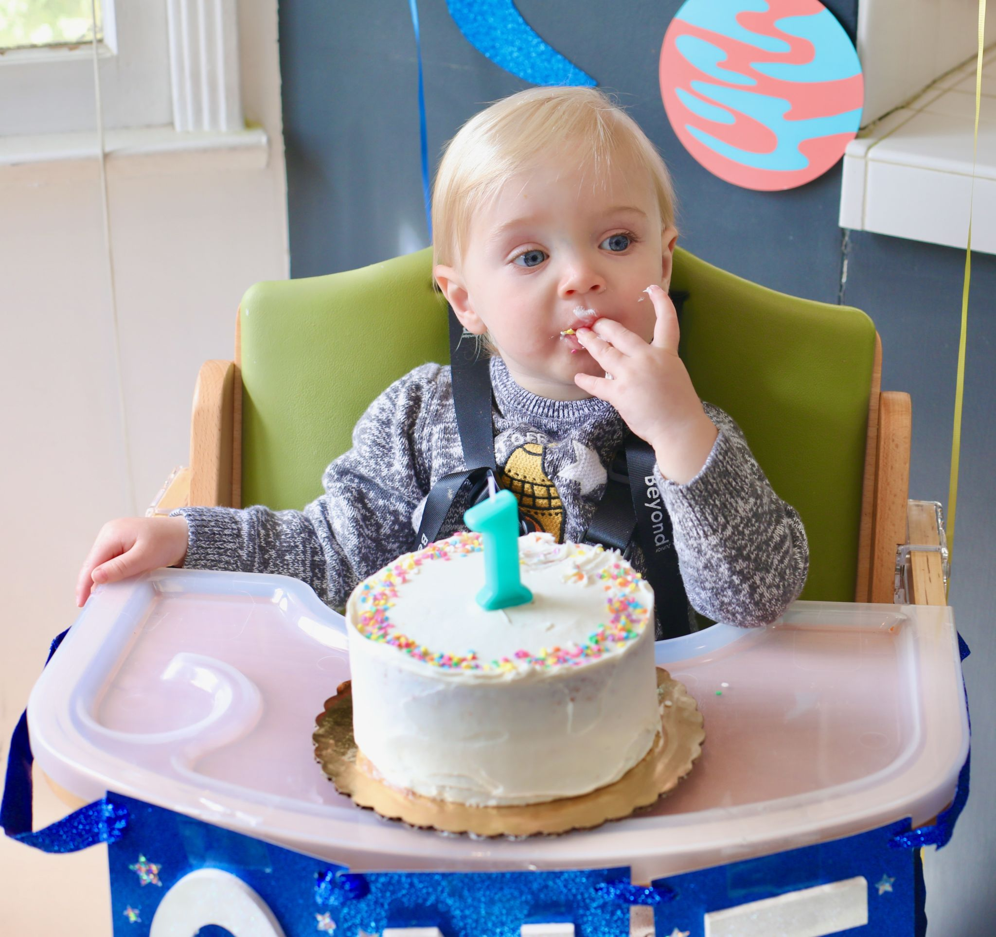A baby with a smash cake and a candle that's the number one.