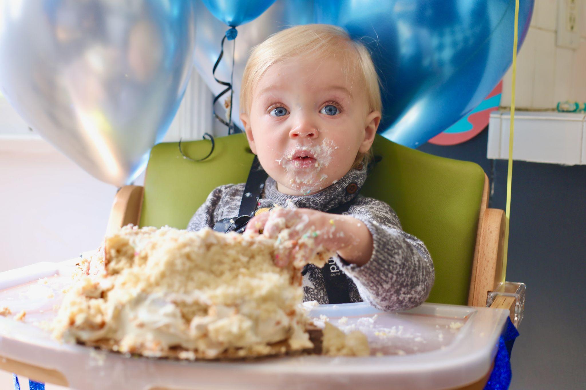 A baby eating a smash cake.
