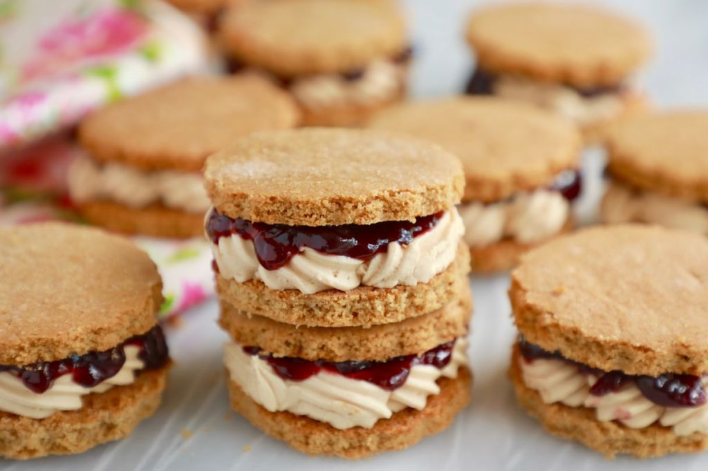 Peanut Butter and Jelly Sandwich Cookies are the perfect marriage of sweet and salty. Soft, crumbly cookie with a soft buttercream and jam center.