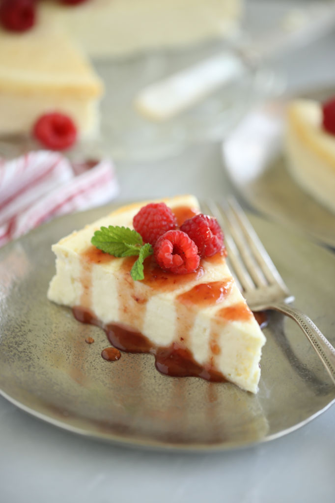 A slice of sugar free baked cheesecake, with raspberries.