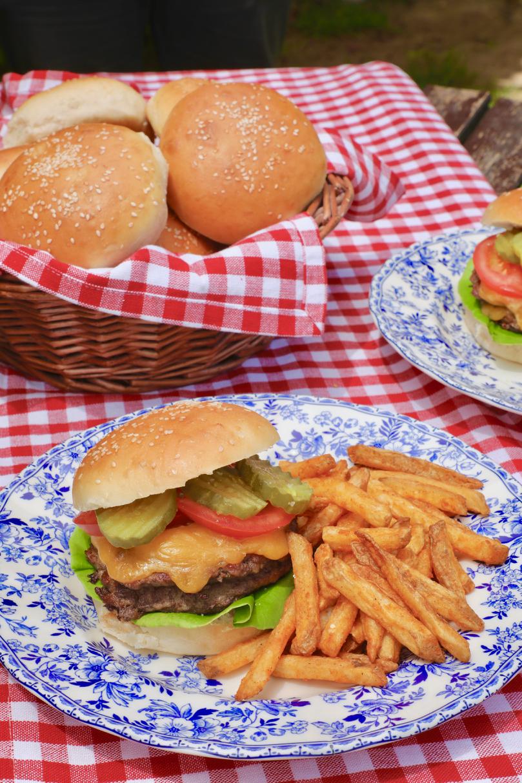 A delicious burger, ready to eat, using a homemade hamburger bun — and fries!