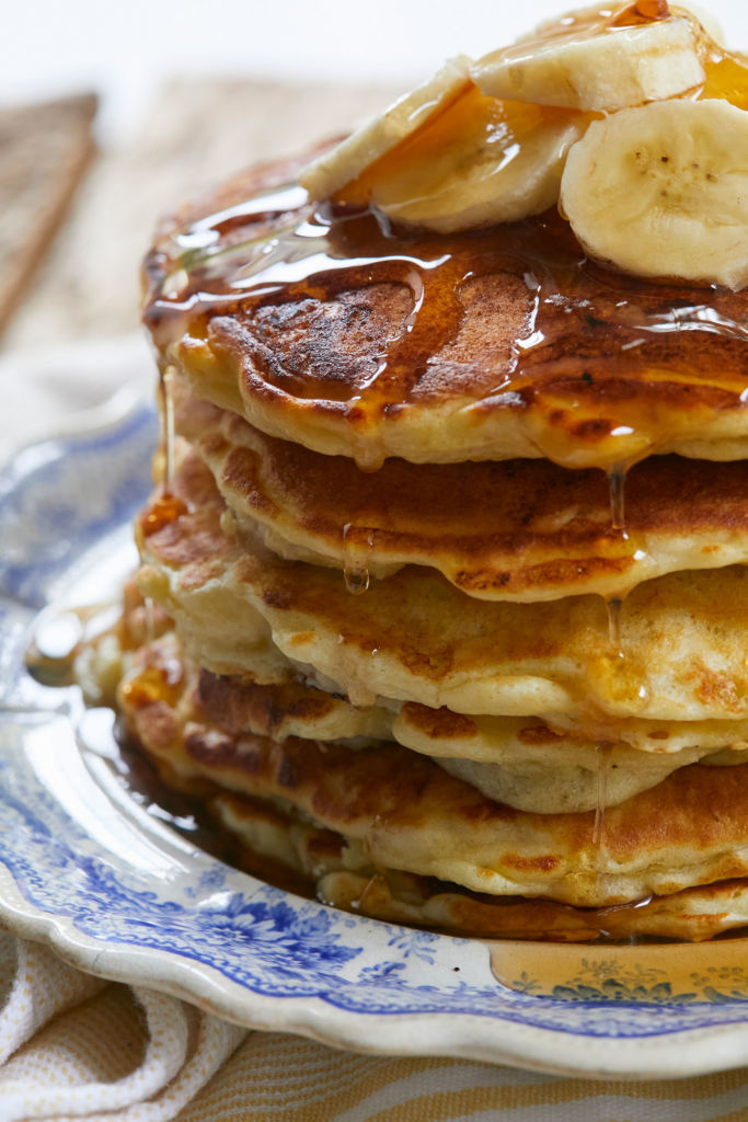 A close up of my Banana Pancakes recipe, dripping with syrup, stacked with bananas, ready to eat.