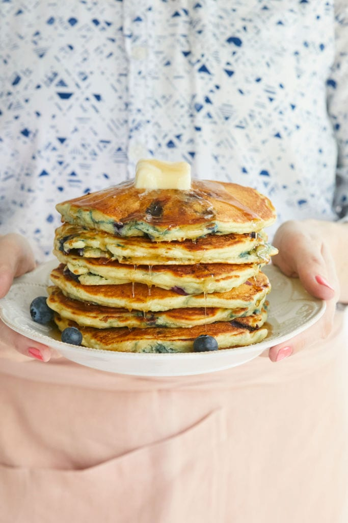 Gemma Stafford holding a stack of her Homemade Blueberry Pancakes recipe.