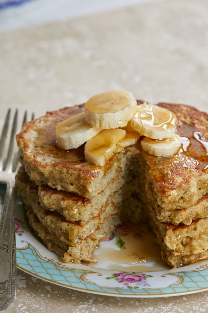 A cross section of flourless pancakes, made with oats, stacked high and topped with bananas and syrup.