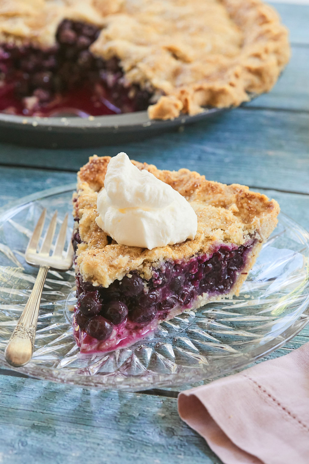 A slice of the best blueberry pie, topped with whipped cream, showing color, texture, and consistency.