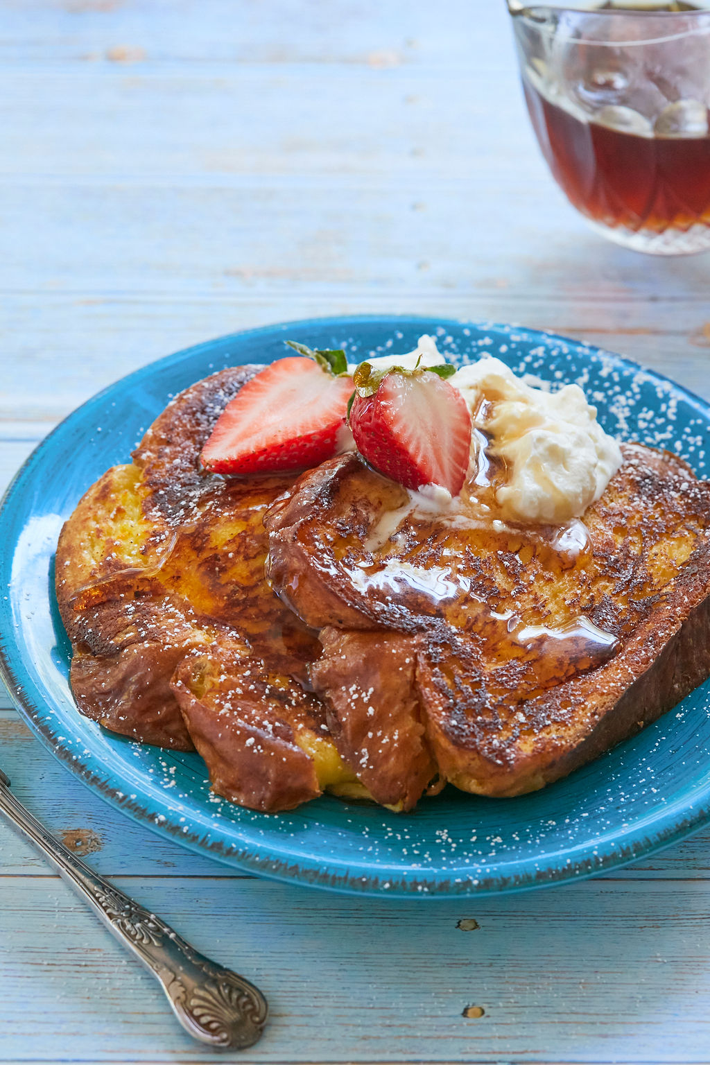 A plate of Brioche French toast topped with cream and strawberries and syrup.