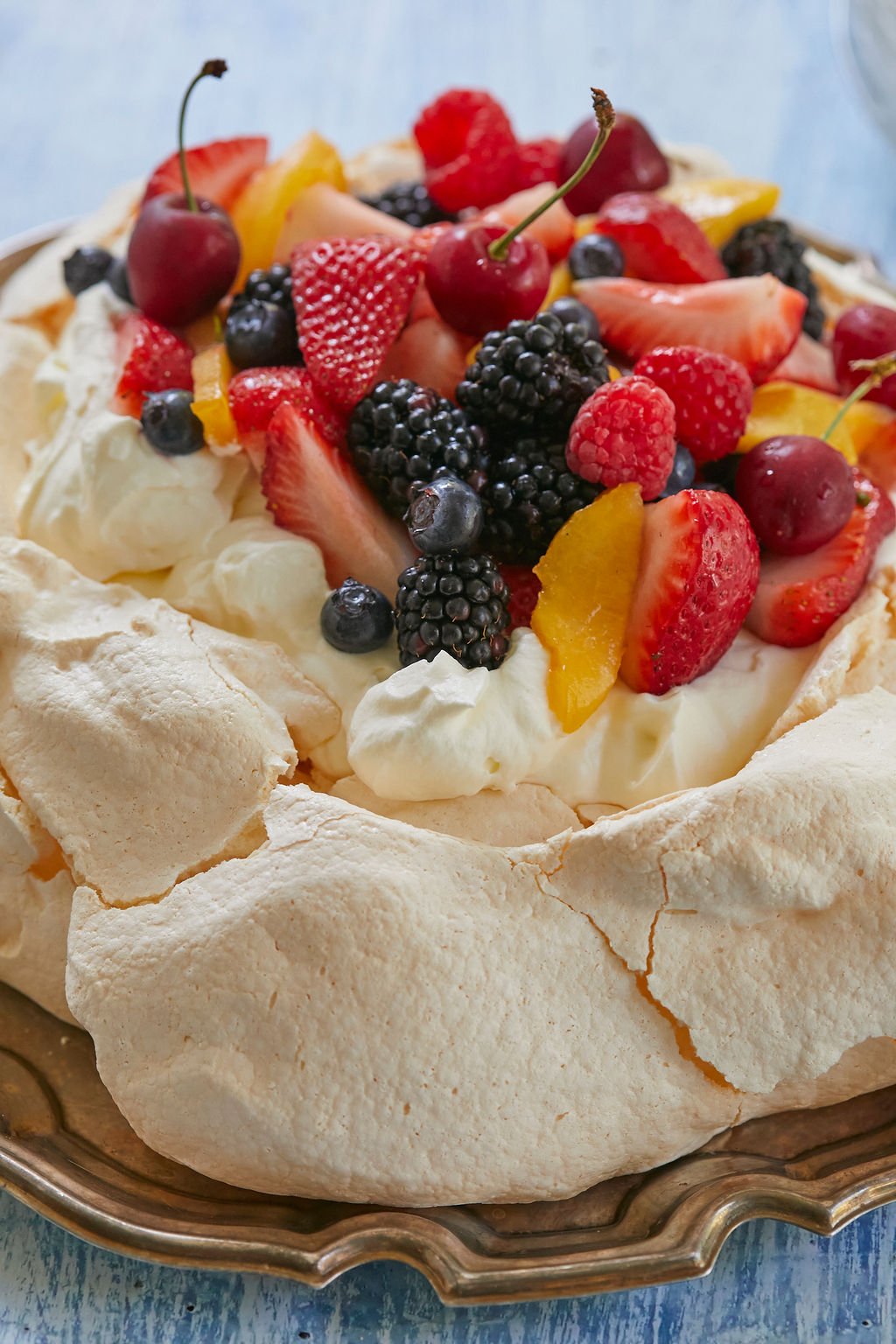 A close-up of the crunchy exterior of my Perfect Pavlova recipe, topped with cream and fruit.