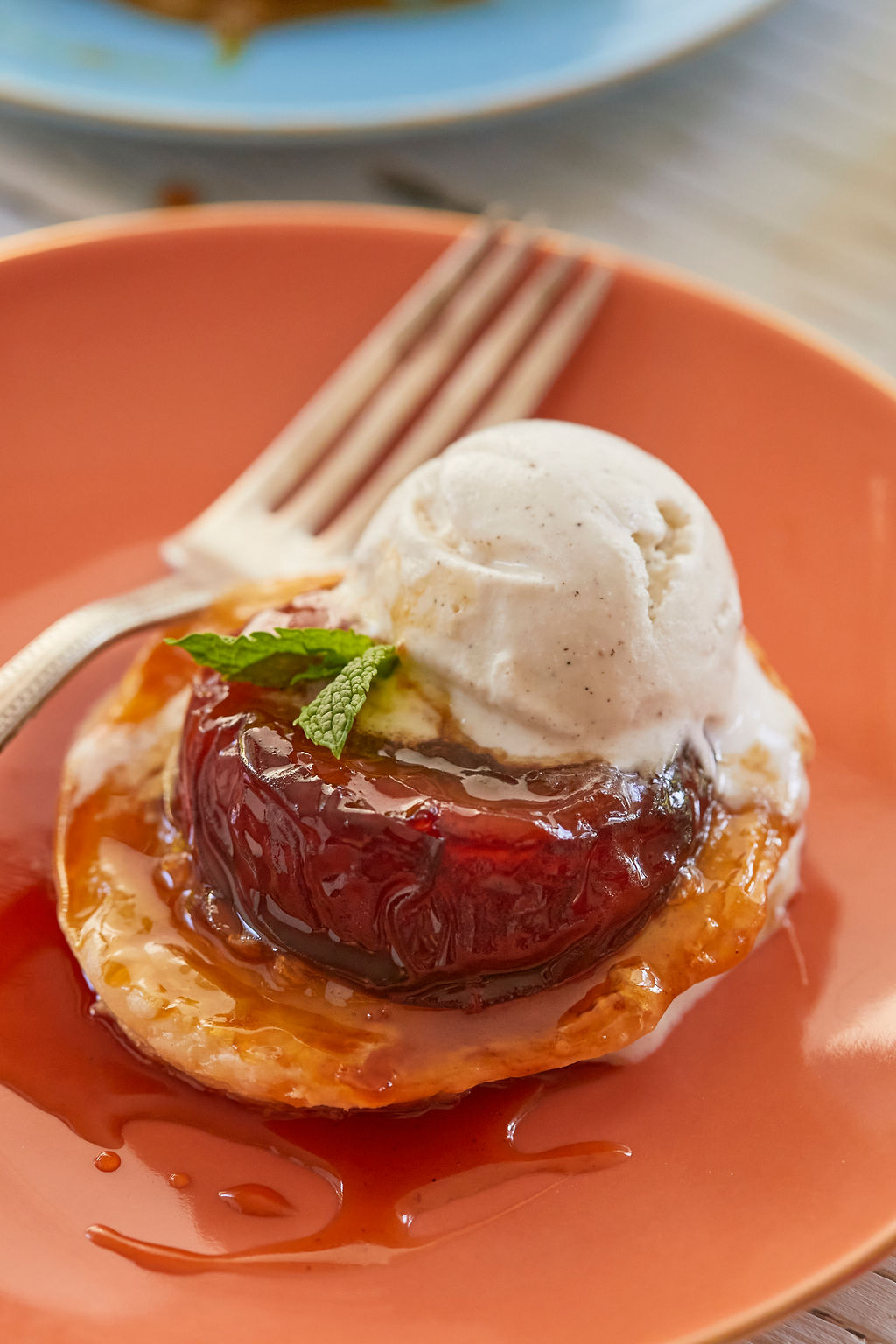 A close up of Homemade Peach Tarte Tatin, topped with vanilla ice cream, to show texture and consistency.