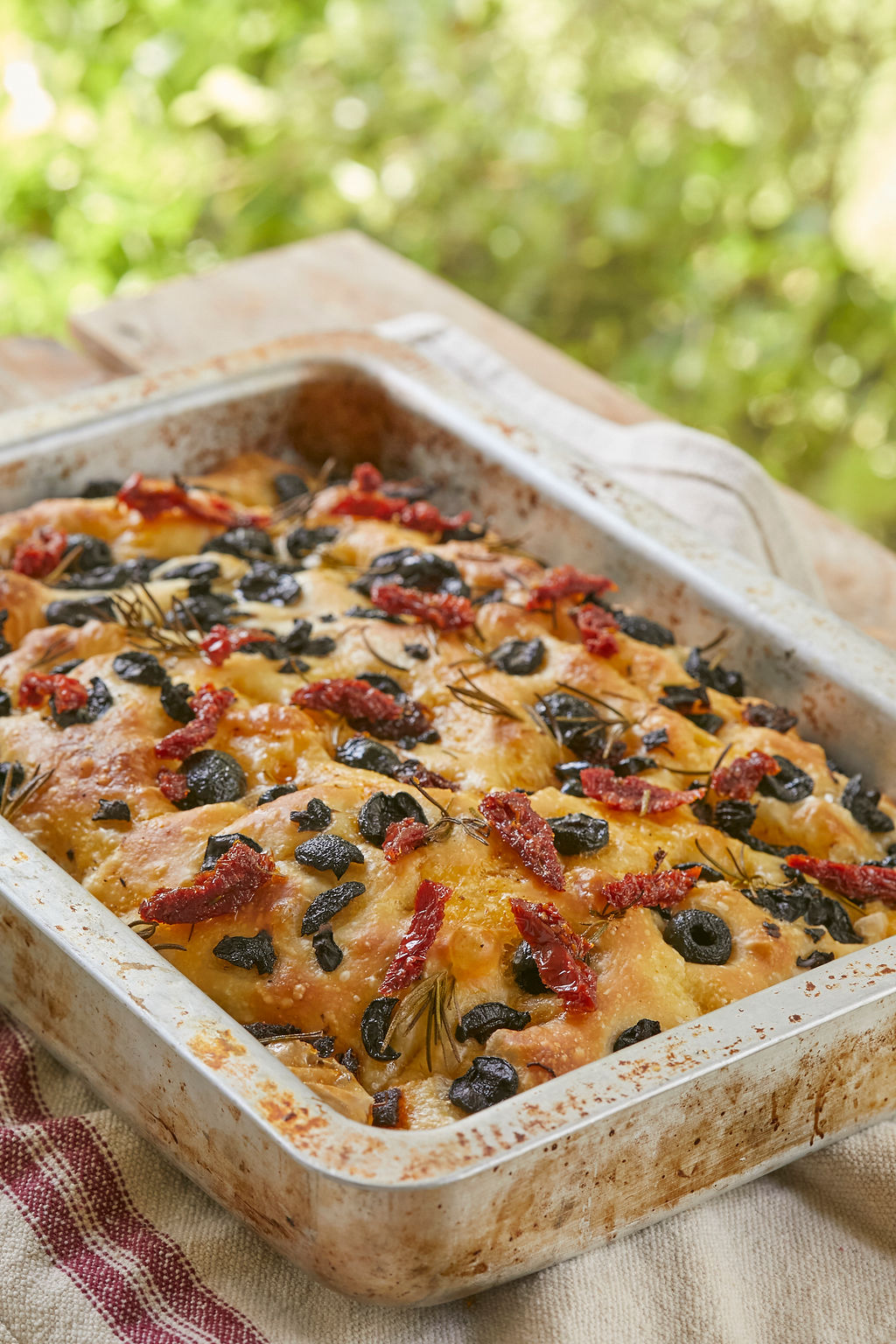 My Sourdough Focaccia baked and ready to cut into slices, topped with olives and sun-dried tomatoes.