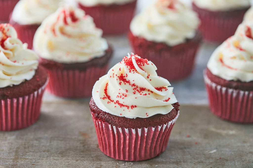 A group of red velvet cupcakes topped with frosting