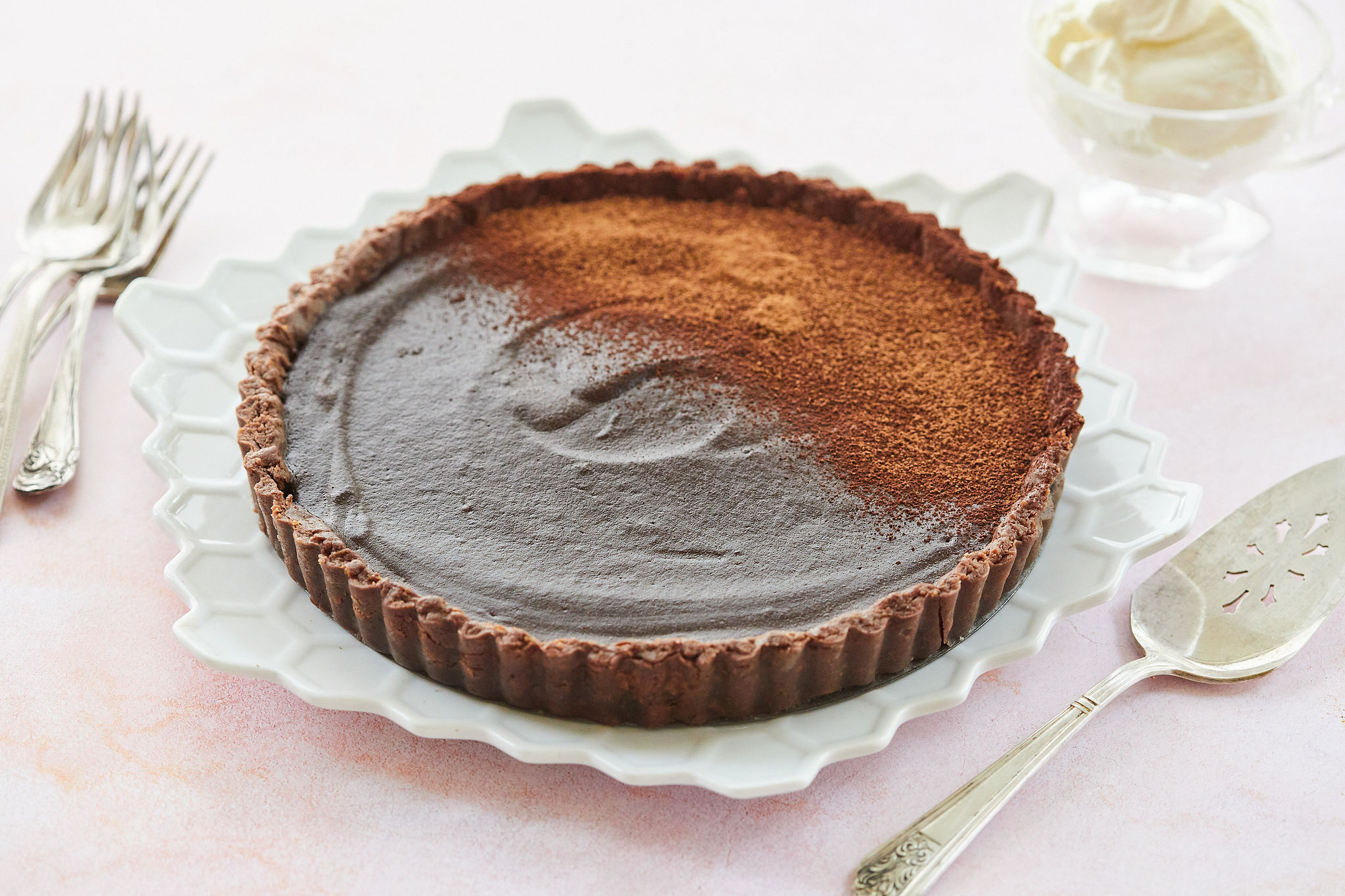 The whole Chocolate Tart on a platter ready to cut and serve.