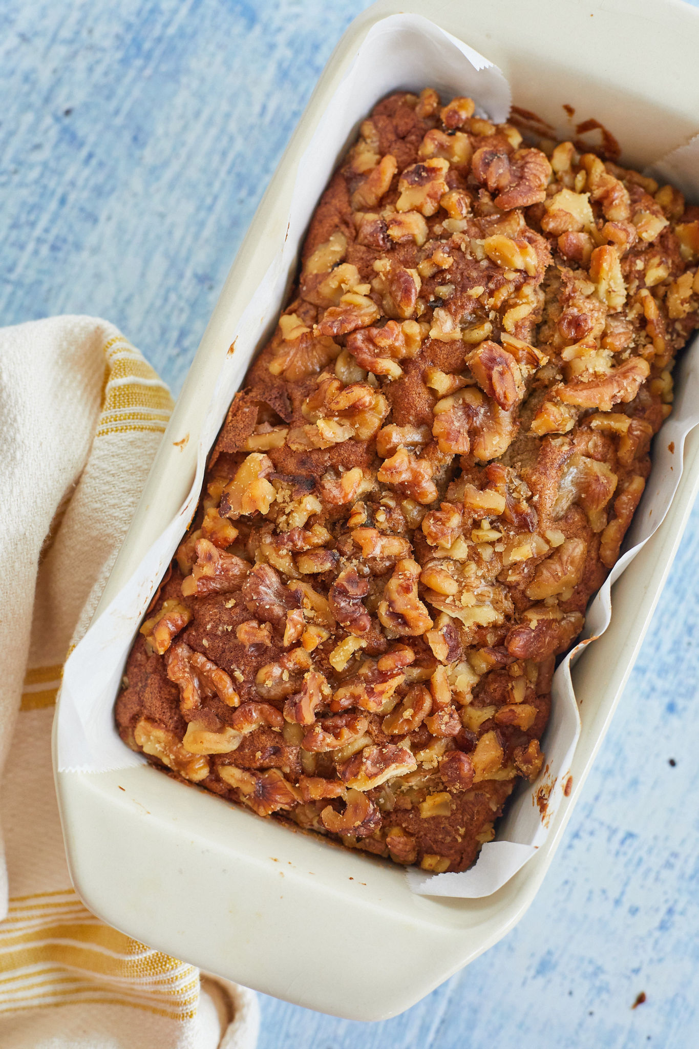 The top of Mia's Banana Nut Bread recipe covered in walnuts.