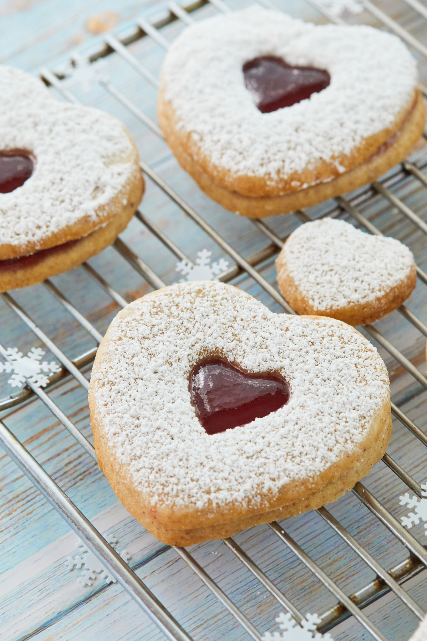 A close up of a Linzer cookie with jam filling.