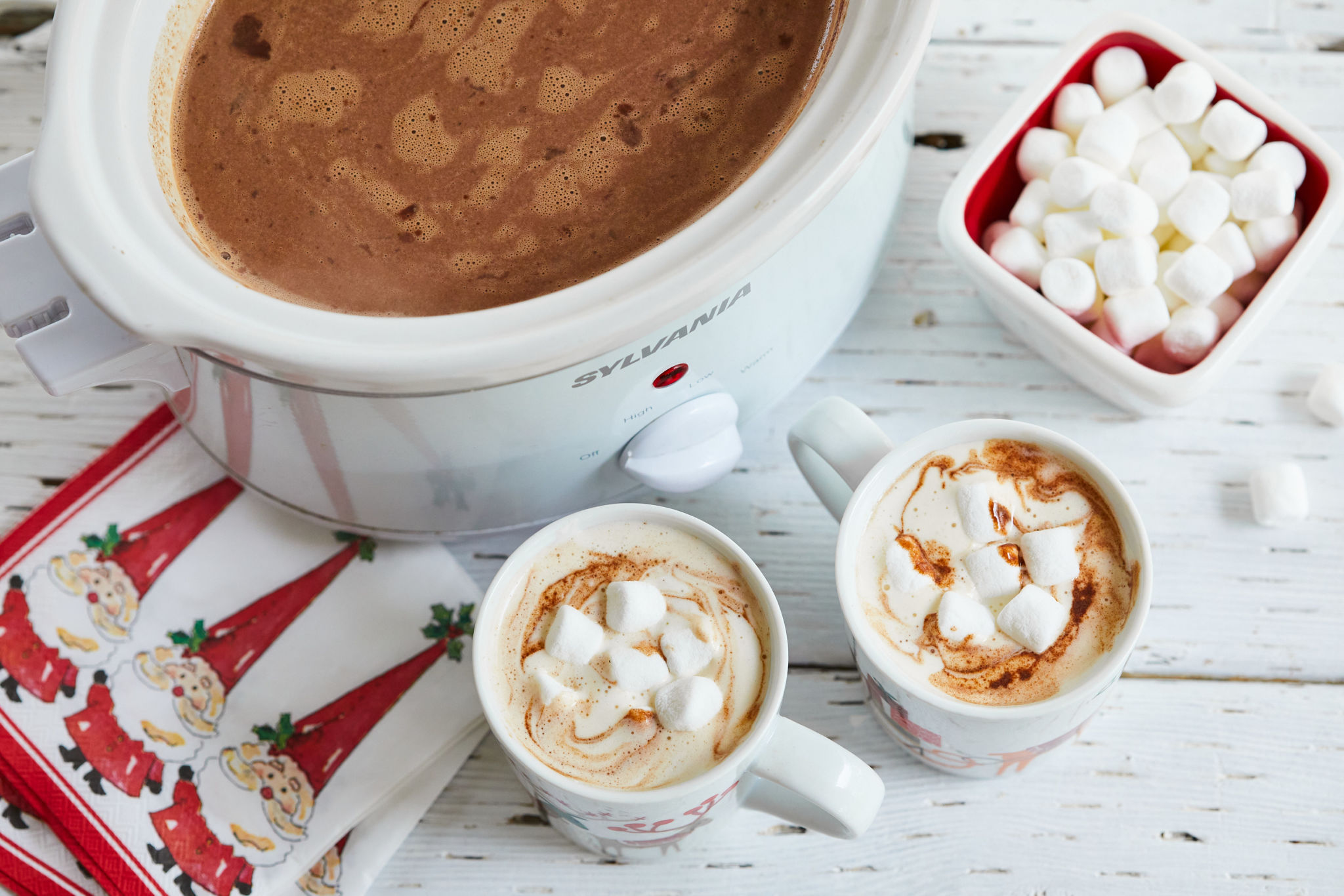A slow cooker full of hot chocolate next to two mugs and a bowl of marshmallows.