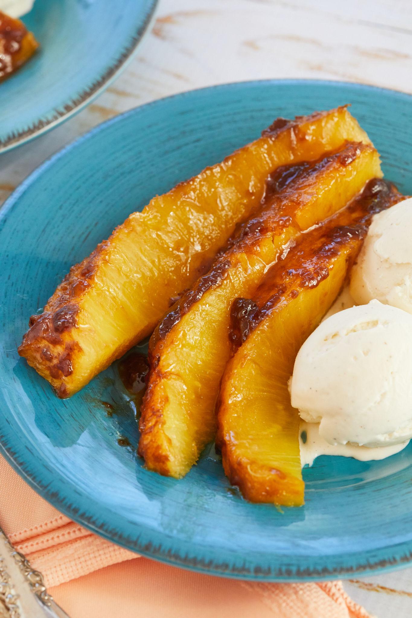 Slices of roasted pineapple with vanilla ice cream.