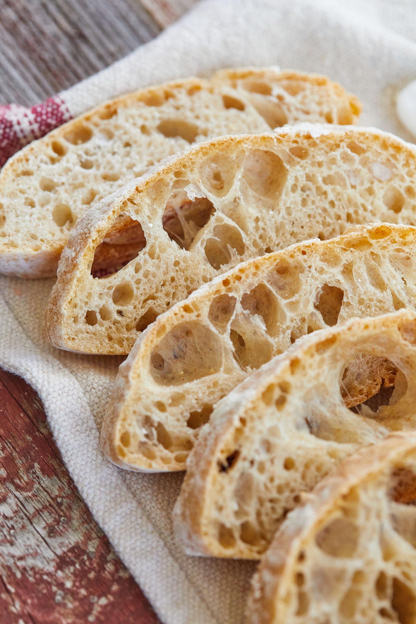 Slices of no-knead ciabatta bread spread out on a cloth.