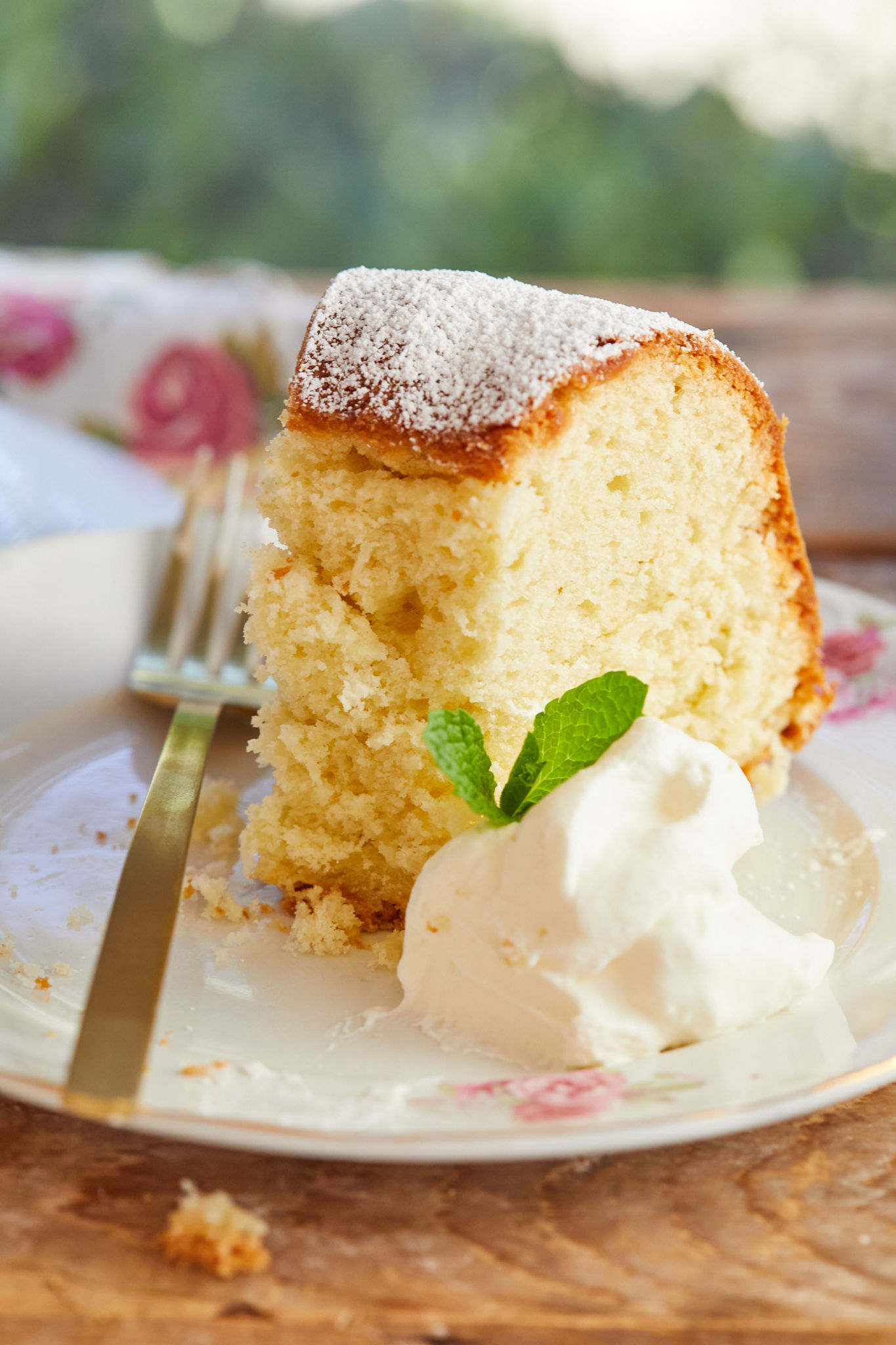 A close up of a slice of Coconut Cream Cheese Pound Cake with a dollop of fresh whipped cream.