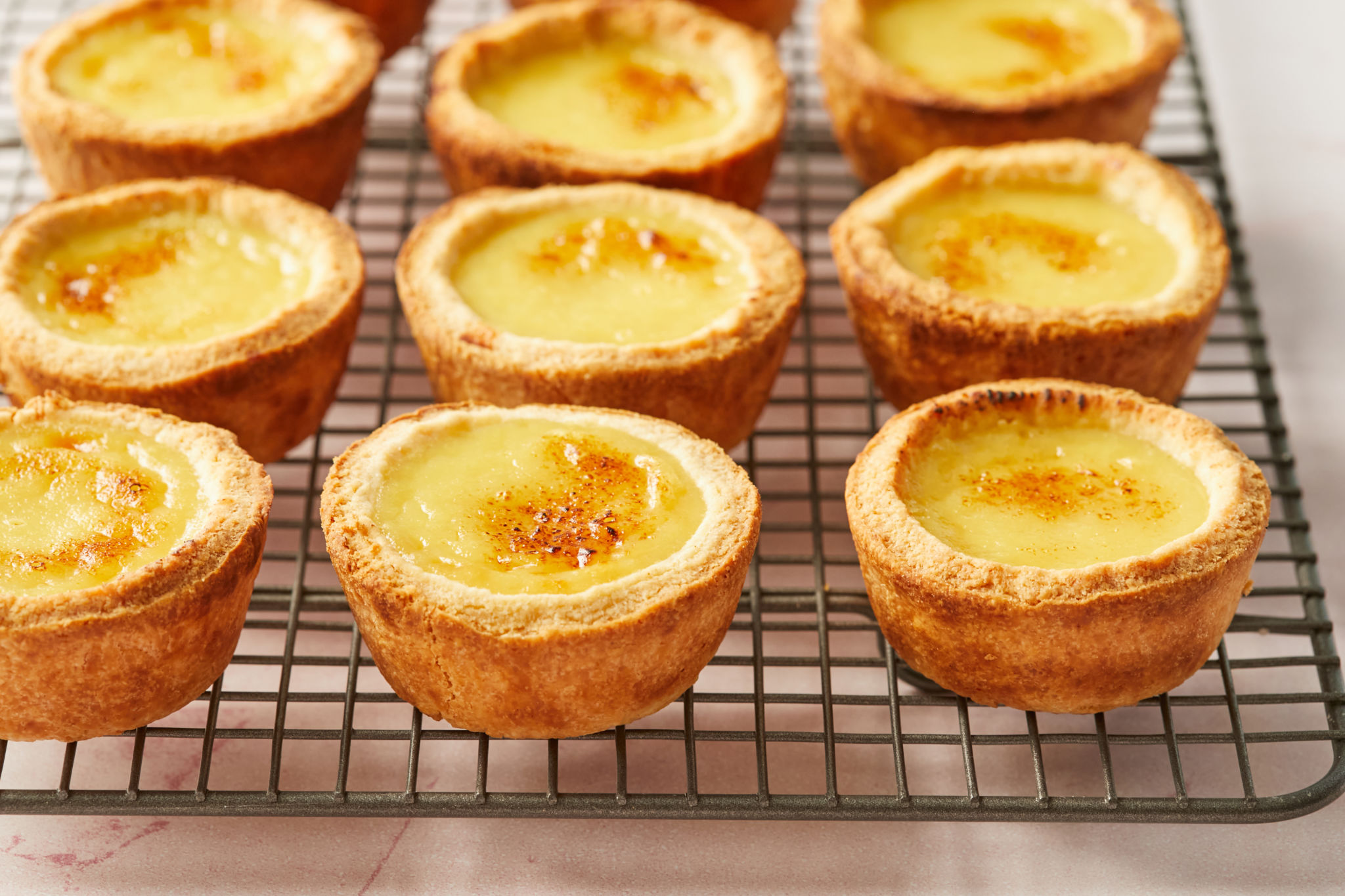 Rows of Portuguese Custard Tarts on a wire rack.