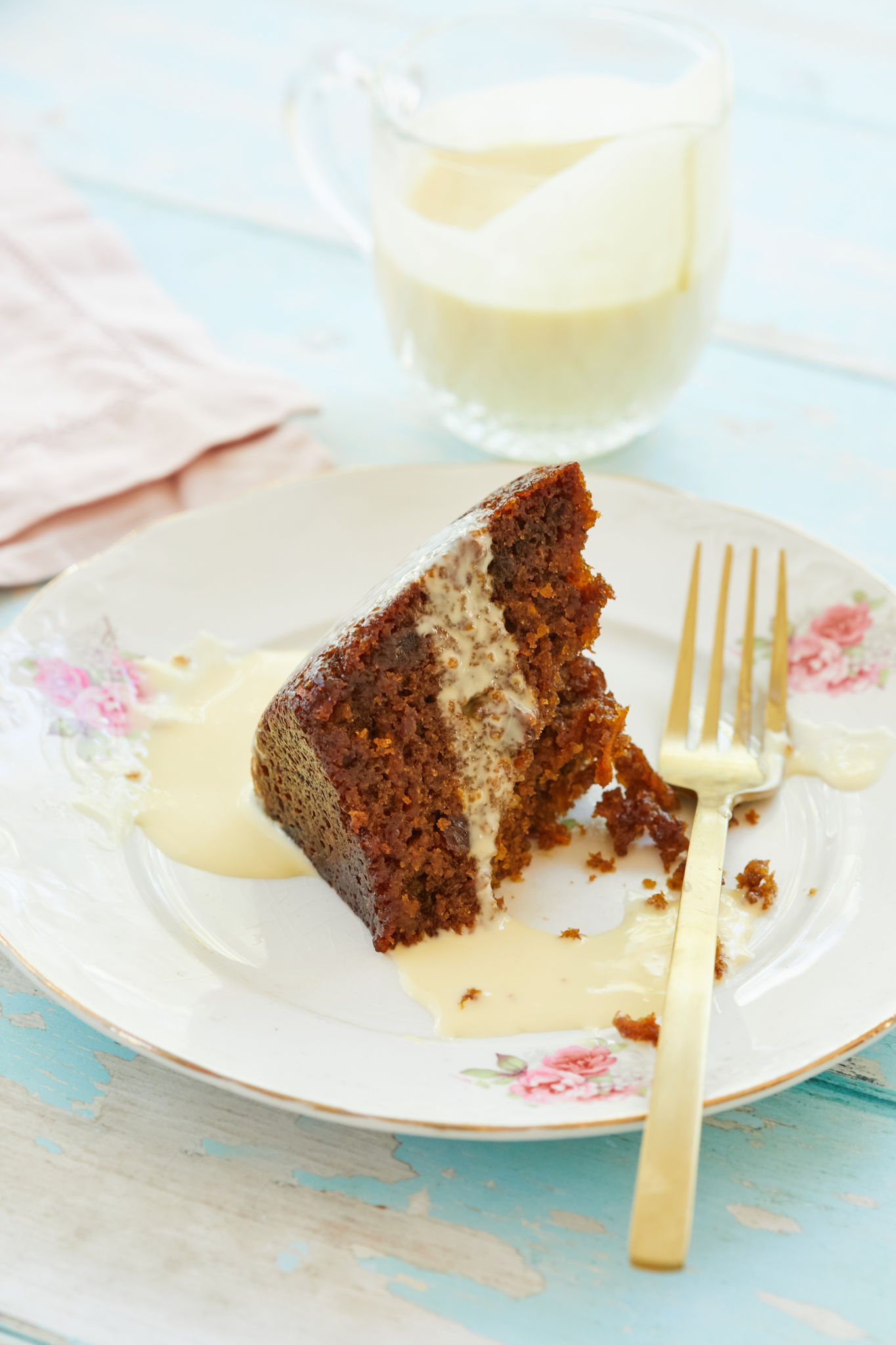 A slice of steamed carrot pudding topped with creme anglaise.