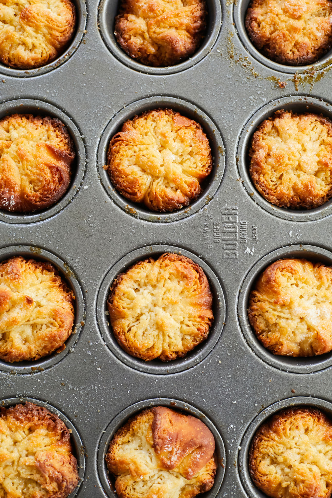 A muffin tin filled with baked Kouign-Amann pastries.