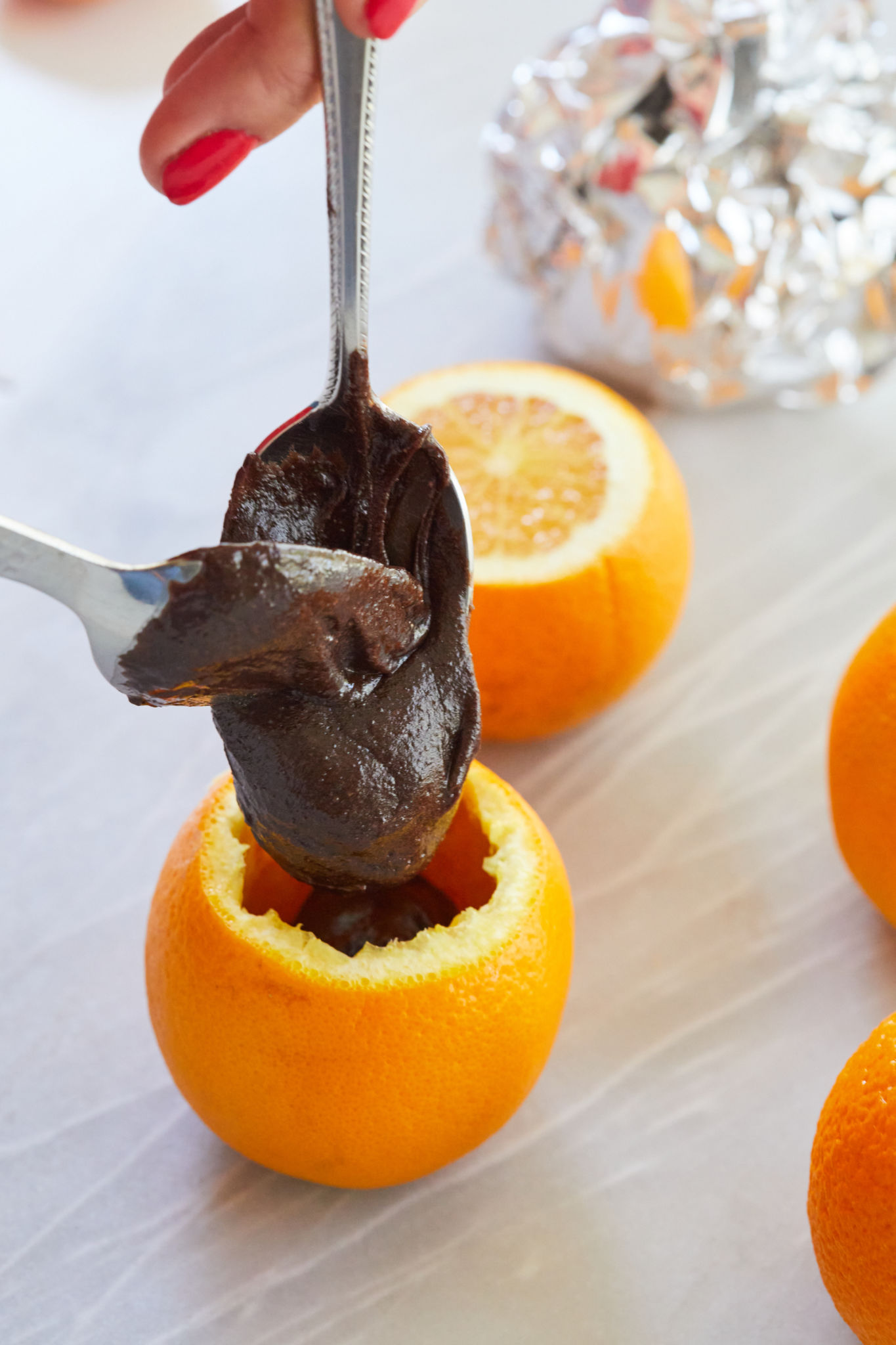 Spoons pouring batter into the shell of an orange.