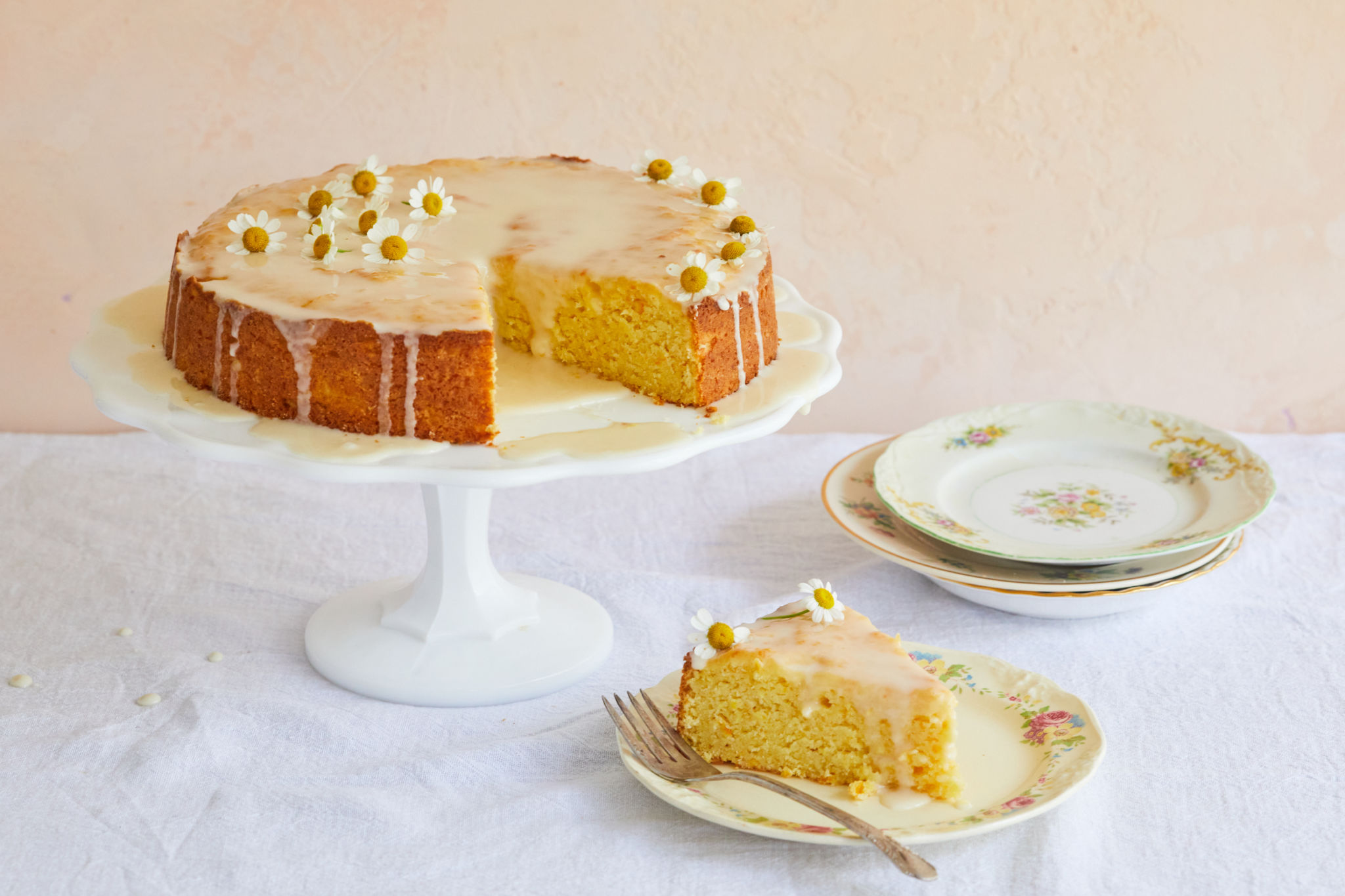 A whole orange cake with a slice removed.